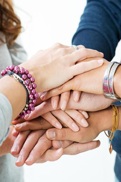 8 Hände liegen aufeinander
