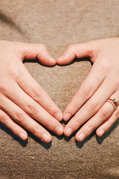 Hände formen ein Herz auf dem Bauch