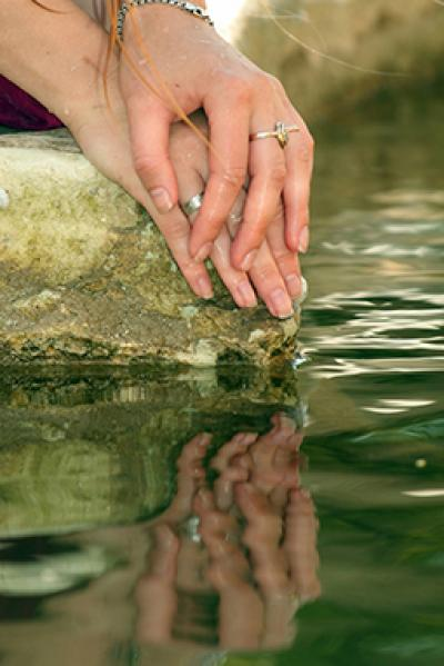 Zwei Hände liegen auf einem Stein im Wasser