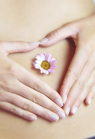 Hände mit Gänseblümchen am Bauch